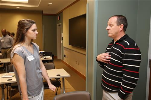 Chatham Middle School principal Chad Morgan speaks with a prospective  teacher during a recruiting event.