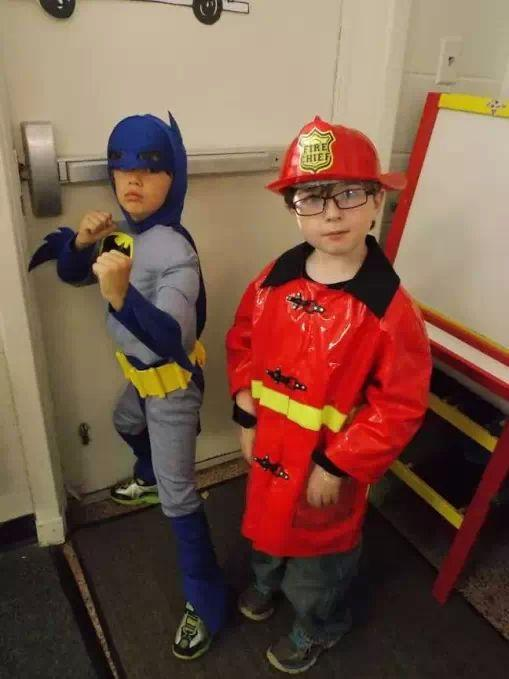 Boys showing off their batman and fireman outfits