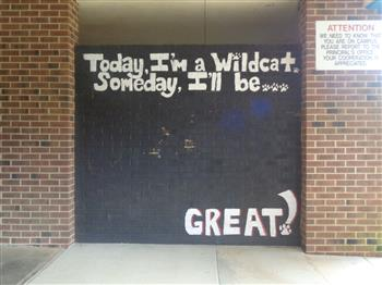 White text is displayed on a black wall. The text says: Today I'm a Wildcat. Tomorrow I'll be great!